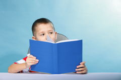Child boy kid reading a book on blue. Young boy reading a book, child kid on blue background holding an open book Stock Photo