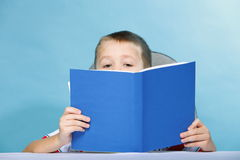 Child boy kid reading a book on blue Royalty Free Stock Photos
