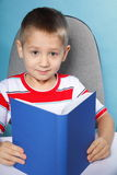 Child boy kid reading a book on blue Stock Photos