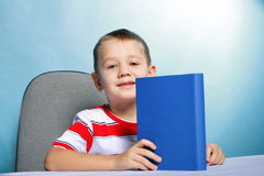 Child boy kid reading a book on blue Stock Images