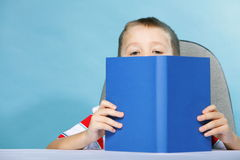 Child boy kid reading a book on blue. Young boy reading a book, child kid on blue background holding an open book Stock Image