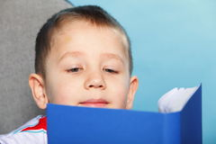 Child boy kid reading a book on blue. Young boy reading a book, child kid on blue background holding an open book Royalty Free Stock Image