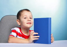 Child boy kid reading a book on blue Stock Photography
