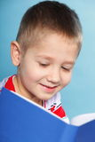 Child boy kid reading a book on blue Royalty Free Stock Photo