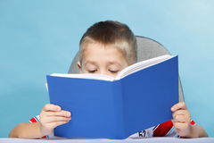 Child boy kid reading a book on blue Stock Image