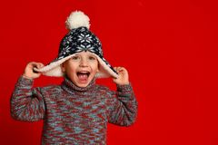 Child boy in knitted hat and sweater having fun over colorful red background. stock images
