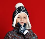 Child boy in knitted hat and sweater and mittens having fun over colorful red background. royalty free stock image