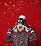 Child boy in knitted hat and sweater and mittens having fun over colorful red background. royalty free stock photography