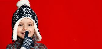 Child boy in knitted hat and sweater and mittens making silence gesture over colorful red background. stock photo