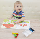 Child boy learning to use colorful play clay in nursery.  Royalty Free Stock Photography