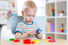 Child boy learning to use colorful play clay in nursery room. Child boy learning to use colorful play clay in nursery Royalty Free Stock Photo