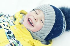 Child, boy, lies on the snow, blurred picture, emotions stock photo
