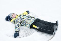 A child, a boy, lies on the snow, makes a snow angel with his arms and legs, emotions, laughs stock photos