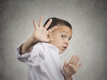 Child boy looking scared trying to protect himself. Closeup portrait child boy looking shocked scared trying to protect himself from unpleasant situation, object Royalty Free Stock Image