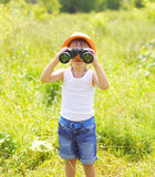 Child boy looks in binoculars outdoors in summer. Day Royalty Free Stock Image