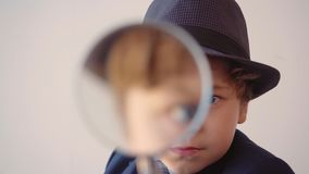 Child boy looks like a businessman in hat and suit in his office is looking through magnifier.