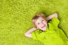 Child Boy lying on green carpet background. Smiling Kid Royalty Free Stock Images