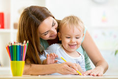 Child boy and mother draw with colorful pencils Royalty Free Stock Photo