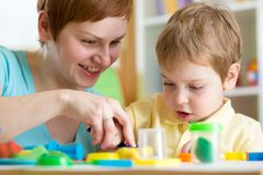 Child boy and mother playing colorful clay toy Royalty Free Stock Photo