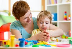 Child boy and mother playing colorful clay toy Royalty Free Stock Photography
