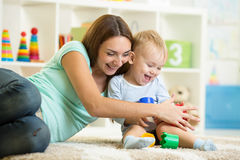Child boy and mother playing together with toys at Royalty Free Stock Photo