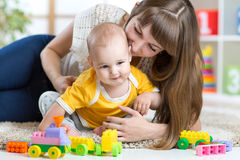Child boy and mother playing together with toys at Stock Photos