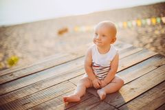 Child boy one year blond sits on a wooden dock, a pier in striped clothes, a compound near the pond on a sandy beach against a bac royalty free stock photography