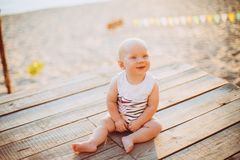 Child boy one year blond sits on a wooden dock, a pier in striped clothes, a compound near the pond on a sandy beach against a bac royalty free stock images