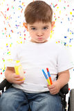 Child Boy Paint Wheelchair. Adorable 2 year old boy in wheelchair holding paint and brushes on paint splattered background royalty free stock photo