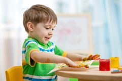 Child boy painting at home. Cute child boy painting at table indoors Royalty Free Stock Image