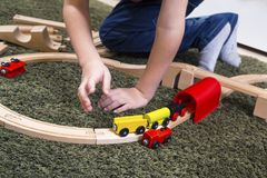 Child boy play with wooden train, build toy railroad at home or. Children play with wooden toy, build toy railroad at home or daycare. Toddler boy play with Royalty Free Stock Image