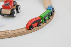 Wooden train, build toy railroad at home or daycare. Wooden toy train with colorful blocs on white background. Child boy play with wooden train, build toy royalty free stock photography