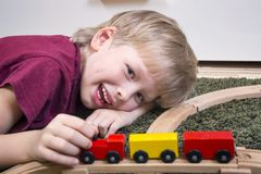 Child boy play with wooden train. Children play with wooden toy, build toy railroad at home or daycare. Toddler boy play with  train and cars. Educational toys Royalty Free Stock Photos