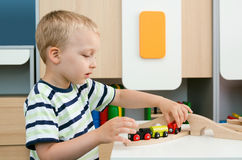 Child boy play with wooden train in kindergarten Royalty Free Stock Photo