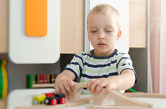 Child boy play with wooden train in kindergarten Stock Photos