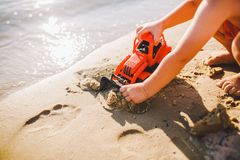 Child boy playing on the beach near the river toy red tractor Royalty Free Stock Photos
