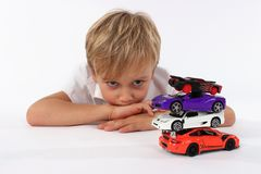 A child boy playing with car toys. Playtime for children. A boy with an attitude of boredom stock photos