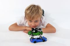 A child boy playing with car toys. Playtime for children. A boy with an attitude of boredom stock photo