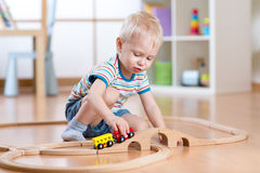 Child boy playing in his room with a toy train Royalty Free Stock Photo