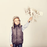 Child boy playing with paper toy airplane and dreaming of becomi Stock Images