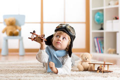 Child boy playing with toy airplane and dreaming of becoming a pilot Royalty Free Stock Photos