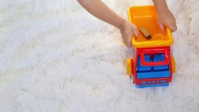 Child boy playing with a toy truck close-up, in slow motion, on a white background. Slow motion stock video footage