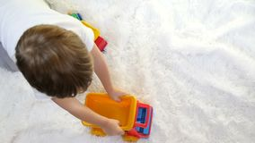 Child boy playing with a toy truck, in slow motion, on a white background. Slow motion stock video