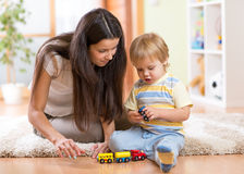 Child boy playing with toys indoors at home. Child boy and his mother playing with toys indoors at home stock photography