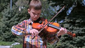 Portrait of child boy is playing the violin standing in park on pine background. Child boy is playing the violin standing in park in the city. Portrait of stock video footage