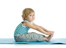 Child boy practicing yoga, stretching in exercise. Kid isolated over white background. Child boy practicing yoga, stretching in exercise wearing sportswear. Kid stock photography