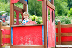 Child boy pretends driving an imaginary car on kids playground Stock Photography