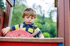 Child boy pretends driving an imaginary car on kids playground Stock Photos
