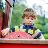 Child boy pretends driving an imaginary car on kids playground Royalty Free Stock Images