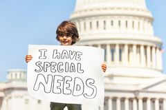 Protester boy holding sign I have special needs. Child boy protest in front of the USA capitol in Washington holding sign saying I have special needs stock photo